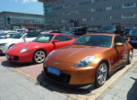 pink-ish Porsche 911 and Nismo Nissan 350Z in China