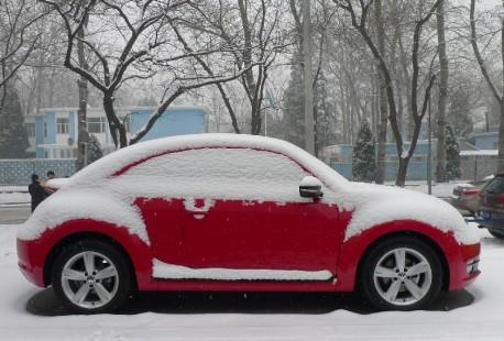 A red Volkswagen Beetle in the Snow in Beijing