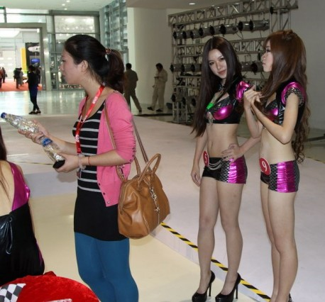 Chinese Car Girls are looking at a Woman holding two Bottles