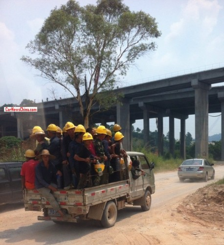 How many Chinese workers wearing yellow helmets can stand in the back of a small truck?