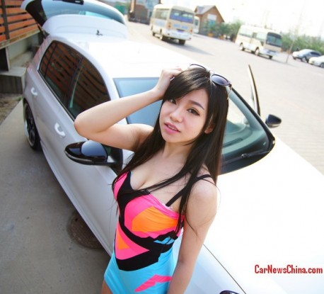 Chinese Girl in colorful miniskirt gets very close to a Volkswagen Golf R
