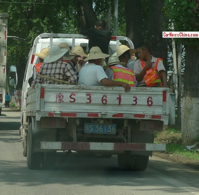 How many people wearing straw hats and/or reflective safety vests fit the back of a small truck in China