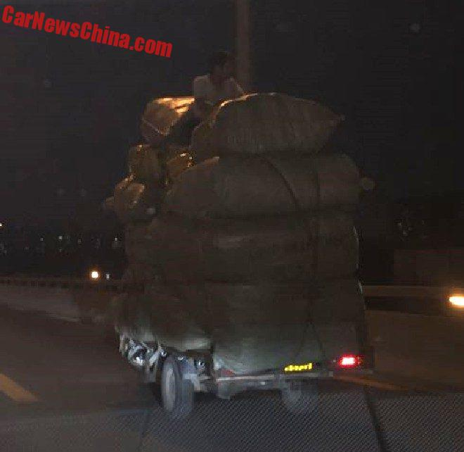 Overloaded Tricycle Is Topped With A Man On A Highway In China