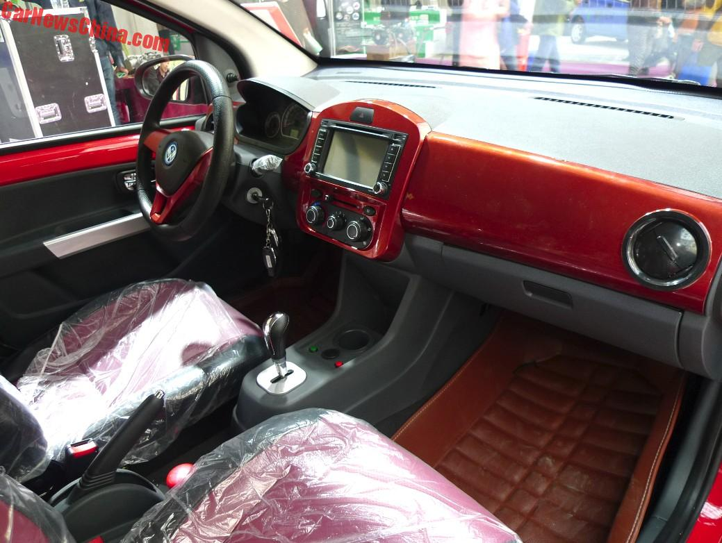 Volkswagen Up Cloned In China Wooden Panel Dashboard It Has An 8 Inch Screen For The Infotainment Wood Colored Panels On Red Black Seats Very Large Air Vents And A Sporty Steering Wheel